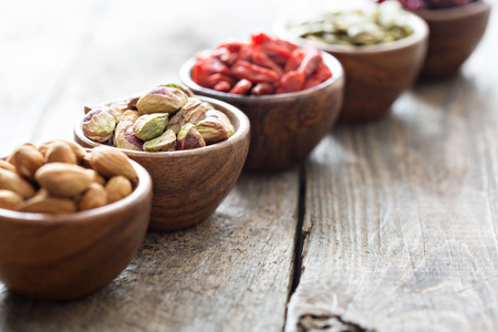 49632671 - variety of nuts and dried fruits in small wooden bowls