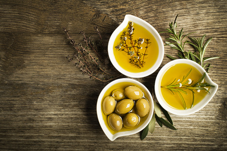 50122488 - olive oil with fresh herbs on wooden background.